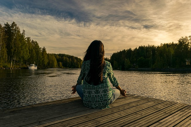 Frau am See sitzend, meditierend